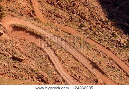 Winding rough rocky dirt unpaved road metaphor for challenge trial struggle