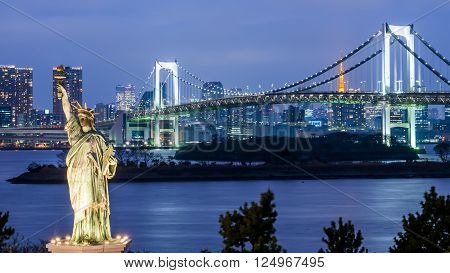 Statue of Liberty and Rainbow bridge located at Odaiba Tokyo with Tokyo skyline in background at twilight