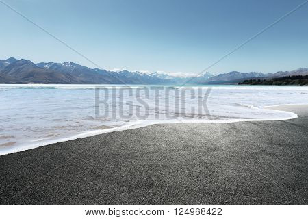 asphalt road covered by seawater in summer day in new zealand