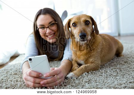 Portrait of beautiful young woman with her dog using mobile phone at home.