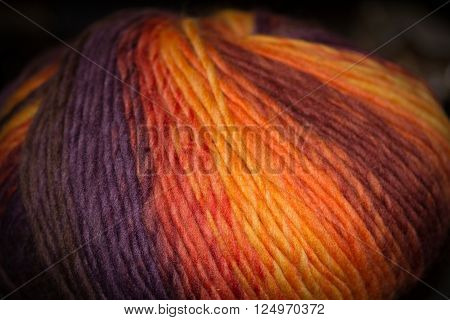 A ball of variegated wool in warm, sunny colors.