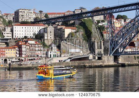 PORTO, PORTUGAL - November 24, 2014: View of the historic city of Porto with the Dom Luis bridge and tourist boat