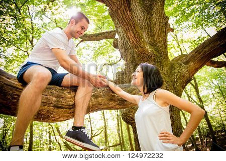 Young man sitting on big tree invites his girlfriend standing bellow