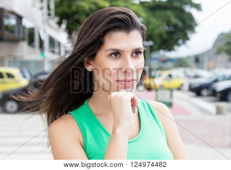 Thinking woman in a green shirt in city with buildings and traffic onn the street in the background
