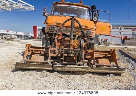 Plate compactor is mounted to the truck compacting sand at road construction site. poster