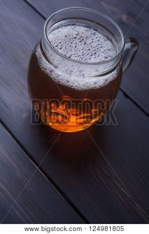 Dimpled mug with amber beer on a dark wooden surface