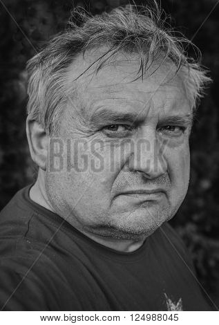 Portrait of a cute old thoughtful man in park