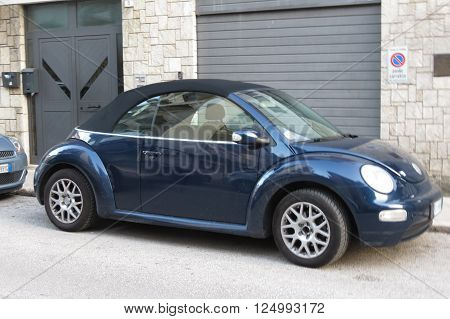 ROME ITALY - CIRCA OCTOBER 2015: blue Volkswagen Beetle cabrio car parked in a street of the city centre