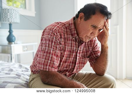 Senior Hispanic Man Sitting On Bed Suffering With Depression