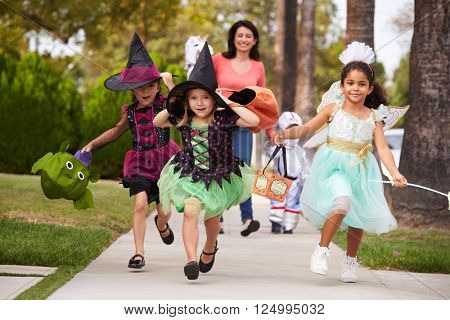 Parent Taking Children Trick Or Treating At Halloween poster