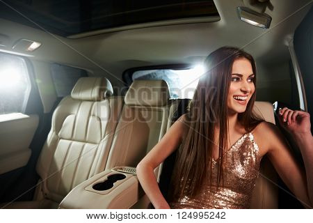 Dark haired young woman sitting in limo looks out of window
