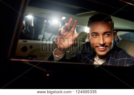Young man waving from the back of a chauffeur driven limo