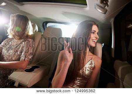 Two women sitting in limo look out of windows, in-car view