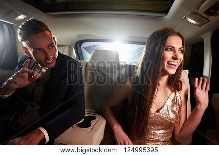 Young couple in the back of a limo looking out of the window