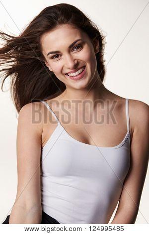 Waist up vertical portrait of dark haired, late teen girl