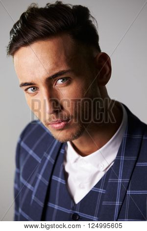 Close-up portrait of inquisitive young man wearing a suit
