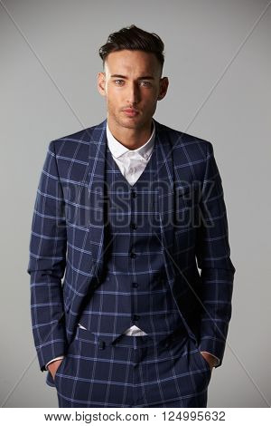 Waist up portrait of young man wearing a large check suit