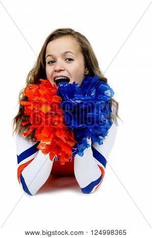 Teenage cheerleader laying down with pom poms