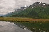 A view of snow-capped mountains and dramatic clouds reflecting off a marsh on the Kenai Peninsula Alaska. poster
