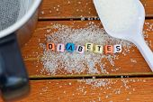 Black mug, spoonful of refined sugar and scattered refined sugar on wooden table. Diabetes concept. poster