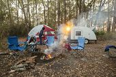 family setting up campsite at sunset with tent and teardrop trailer poster
