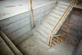 New concrete staircase with temporary wooden handrail under construction. poster