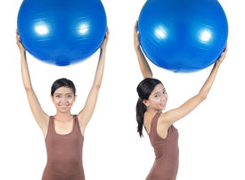 Young woman working out with swiss ball