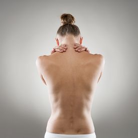 Spine and neck disease. Close-up of naked woman's back suffering from muscle pain.