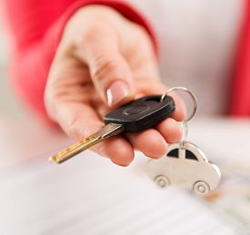 A hand giving car key to buyer in automotive dealer's office