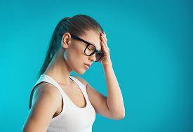 Young female having hangover or vertigo. Studio portrait over blue background. Concept of pain, symptom and health care.