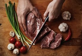 Close-up of raw lamb meat lying on wooden board with garlic, spicy pepper, onion, mushrooms and tomatoes. Male chef with knife chopping tenderloin.