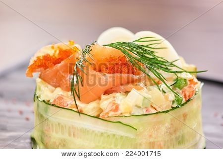 Olivier salad with salmon and tobiko caviar. Tasty olivier salad served with salmon, tobiko caviar, dill and eggs. Appetizing salad in restaurant.