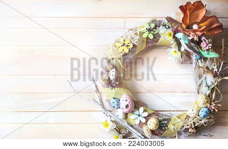 Easter wreath made of straw handmade on a light wooden background