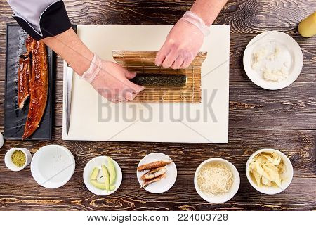Folding sushi in bamboo mat. Preparing sushi. Bamboo mat, preparing sushi, top view.