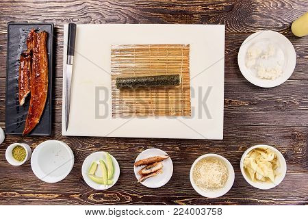 Uncut black sushi roll on bamboo mat. Sushi on bamboo mat on board, knife and other ingredients, top view.