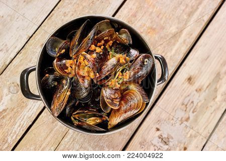 Saucepan of prepared mussels and vegetables. Top view of steamed mussels.
