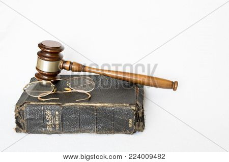 Antique Worn Leather Bible with Antique Eye Glasses and Wooden Gavel on White Background