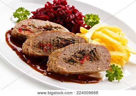 Stuffed meat, French fries and vegetables on white background