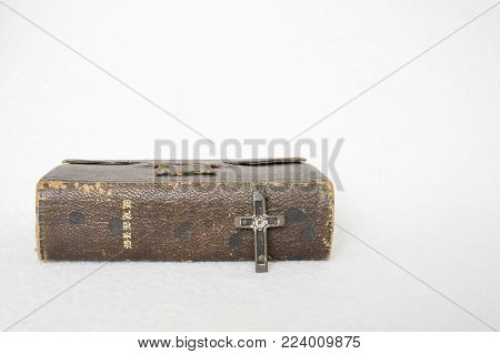 Single Antique Worn Leather Brown Bible with Antique Cross Made of Wood Metal and Nails on White Background