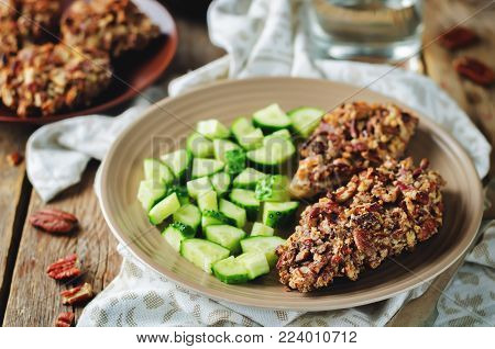 Pecan crust chicken breasts with cucumber's slices on a wood background