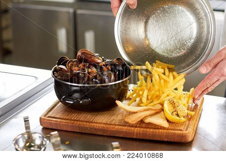 French fries pouring on wooden board. Set of fried mussels, french fries, bread slices and lemon.