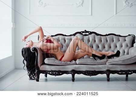Perfect, sexy body, legs and ass of young woman wearing seductive red lingerie. Beautiful hot female in underware posing on luxury vintage sofa.