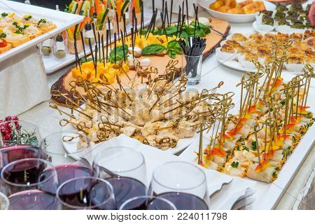 Catering table with food dishes, snacks and alcoholic and non-alcoholic drinks for guests of the event. Service at business meeting, party, weddings. Selective focus