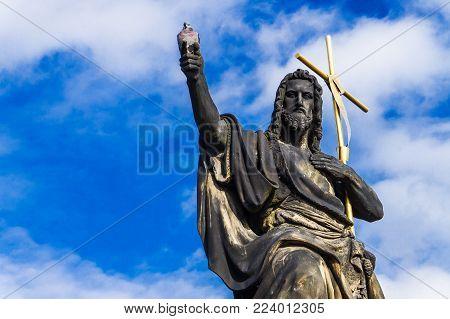 Statue of John the Baptist with golden cross, the sculpture of Charles Bridge in Prague, Czech Republic