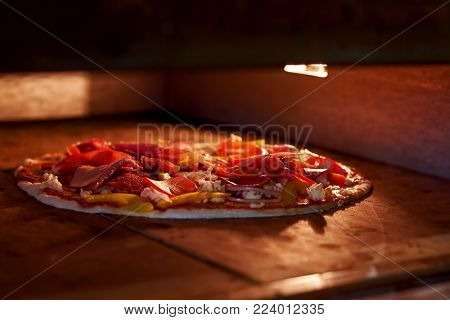 Process of baking pizza inside pizza oven. Close up pizza ingredients inside oven. Salami pizza with vegetables and cheese.