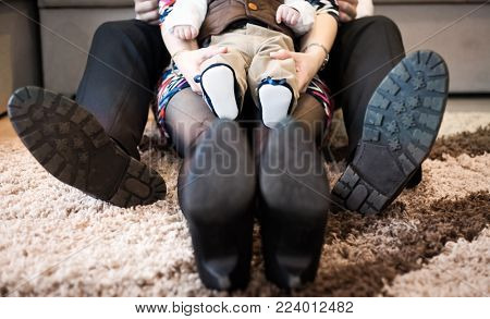 happy family feet - mother, father and baby baby sitting on carpet at home