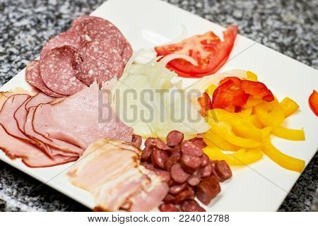 Sliced cold meats and vegetables on white plate. Pizza ingredients assortment, close up. Food assortment.