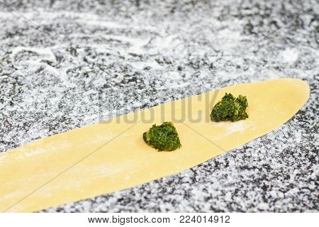 Two little piles of greens on dough sheet. Dough and greens.