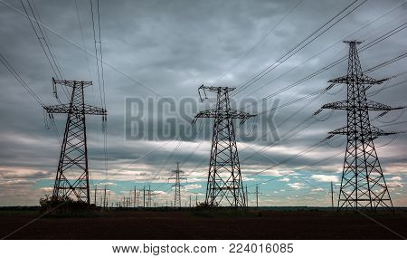high-voltage  power lines at storm clouds. electricity distribution station. high voltage electric transmission tower.