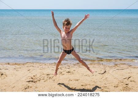 Six-year-old boy in black speedo jumping into the sea and smiles. Jump high off the ground.